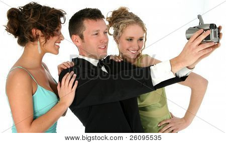 Handsome man in tuxedo with two beautiful young woman, taking photo of group with digital camera. Shot in studio over white.