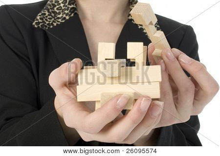 Woman's hand holding wooden puzzle.