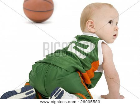 Adorable 10 month old baby boy in basket ball uniform crawling over white floor. Shot in studio.