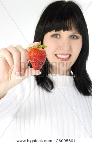 Beautiful young woman holding fresh strawberry. Shot in studio over white.