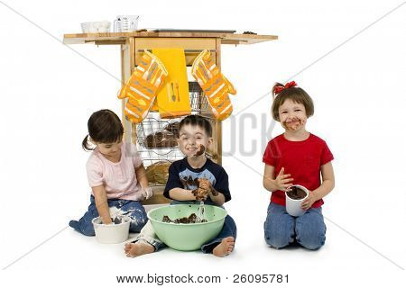 Three adorable toddlers (2, 3 and 4) stirring cake mix. Covered in chocolate batter, flour and eggs. Shot in studio over white.