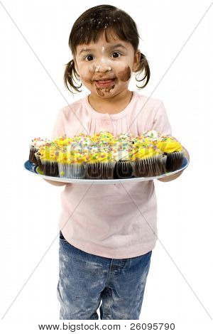 Adorable two year old girl covered in flour holding plate of mini cupcakes.
