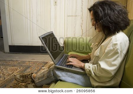 Impoverished middle aged woman working on laptop.