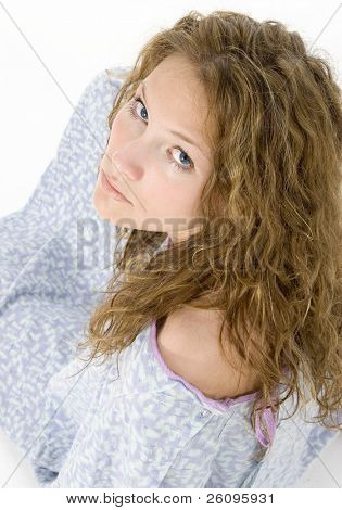 Young woman in hospital gown crying.  Looking over shoulder at camera.  Blue eyes, tears on cheek.