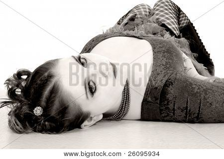 Young goth teen laying on floor looking at camera.  Shot in studio over white.