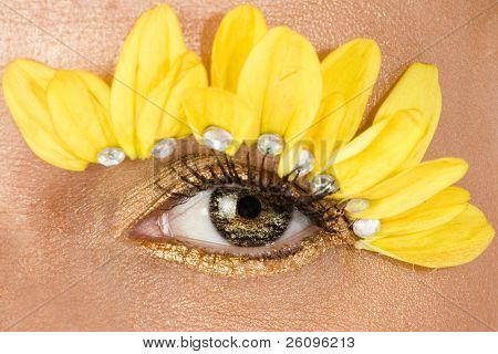 Focus on center eye.  Woman's eye decorated in yellow flowers and gold eyeliner.