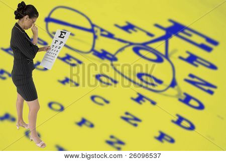 Beautiful woman reading eye chart standing over bright yellow and blue eye chart with glasses.Ophthalmology Ophthalmologist
