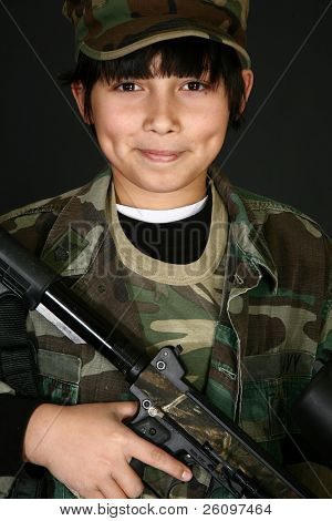 Handsome Filipino  11 year old boy in camo with paintball rifle.