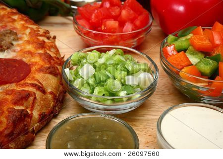Bowl of chopped green onions surrounded by pizza and pizza toppings.
