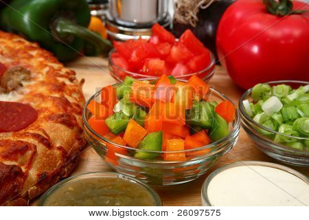 Chopped green and orange bell peppers surrounded by pizza and toppings.