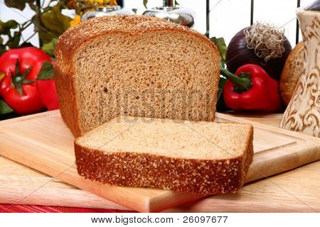 Whole wheat bread sliced on cutting board in kitchen or deli.