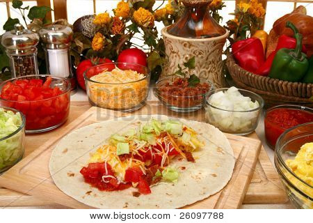 Breakfast burrito in kitchen or restaurant.  Eggs, cheese, tomato, lettuce, onion, chipotle, bacon.