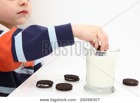 Small boy dunking cookies in milk.