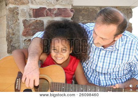 Adorable five year old African American Girl getting guitar lessons.