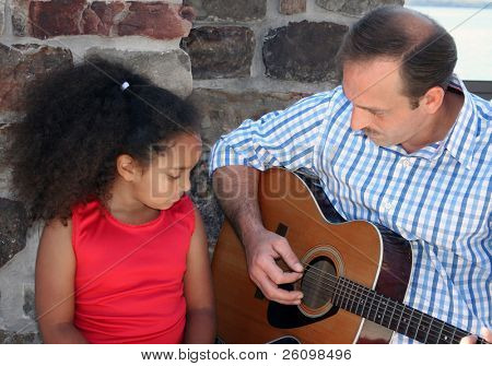 Adorable five year old African American Girl getting guiltar lessons.