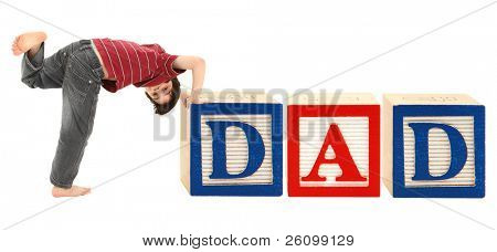 Giant alphabet blocks and adorable seven year old boy spelling out the word DAD