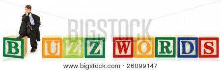 Attractive seven year old boy in over sized suit with word Buzz Words in alphabet blocks.