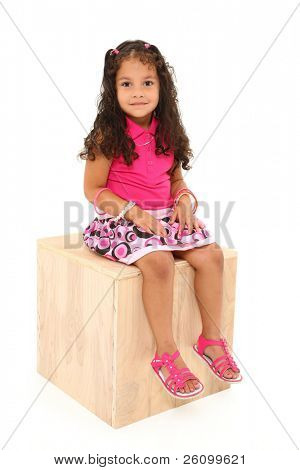 Adorable 3 year old mixed race girl sitting on wooden box over white background.