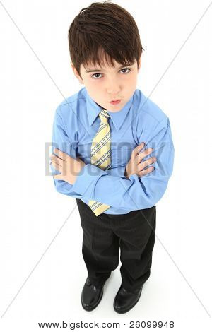 Adorable seven year old french american boy in slacks, dress shirt and tie over white background.