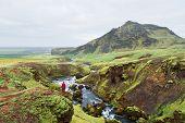 Hiking along the Skoga River, Iceland. Scenic landscape near the Skogafoss Falls. Tourist enjoys a b poster