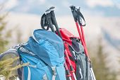 Two Backpacks In The Background Of Snow-capped Mountains And Blue Sky. A Backpack On The Snow. Activ poster