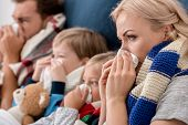 Close-up Shot Of Sick Young Family Blowing Noses With Napkins Together While Lying In Bed poster