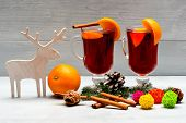 Mulled Wine Or Hot Beverage With Cinnamon Sticks, Orange Fruit And Fir Cone. Glasses With Mulled Win poster