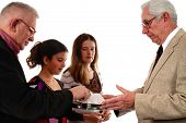 Elderly man passing the bread of communion to three people in the congregation.  Isolated on white.