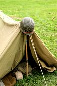 U.s. Army Helmet With Camo Netting Attached Hanging On A Pup Tent At A Reenactment Camp. poster