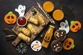 Halloween Food. Scary Sausage Mummies, Gingerbread Cookies, Pumpkin Dessert And Juice On Dark Backgr poster