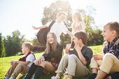 A Group Of Happy Smiling Children Of School And Preschool Age Are Sitting On The Green Grass In The  poster