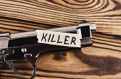 Inscription Killer On Torn Paper And Glossy Pistol On Old Rustic Wooden Weathered Planks poster