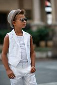 Young boy in hat posing and sun glasses in the milanese streets. Cute happy 6 years old boy posing i poster