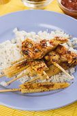Asian spicy  chicken meat on skewer with rice and baby corn poster