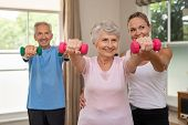 Happy senior couple exercising with dumbbells. Mature personal trainer helping elderly woman exercis poster