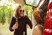 Photo of joyous hippie couple man and woman smiling and drinking beer in forest near retro minivan poster
