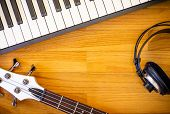 A Wooden Background With A Set Of Musical Instruments Consisting Of A Keyboard, A Bass Guitar And A  poster