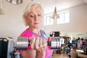 Senior Woman Exercising With Weights In Gym poster