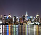 New York City Manhattan midtown skyline at night with lights reflection over Hudson River viewed fro