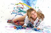 foto of coy  - Beautiful young woman laying in paint covered studio - JPG