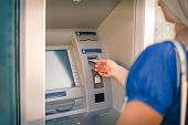 Young Woman Inserting Credit Card Into Atm Machine To Checkout Account Balance And Withdraw Money Fr poster