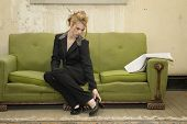 stock photo of rectifier  - Beautiful young Hispanic business woman in suit removes shoes in her impoverished home - JPG