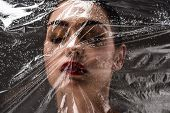 View Through Wet Cellophane At Beautiful Young Woman With Closed Eyes On Black poster