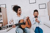 Little Girl Song With Mother. Mother Play On Guitar. Happy Family Play And Sing Together. Relax And poster