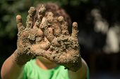 A Cute Little Boy Kid Is  Plays Outside In The Mud. Child Is Showing His Dirty Hands. Very Shallow F poster