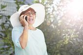 Aged Woman Talking On Phone. Old Lady In The Park. Sunny Day, Happy Mood. Happysenior Woman With Pho poster