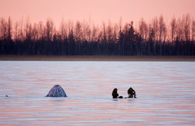 foto of ice fishing  - two fishermen on the frozen lake by the tent - JPG