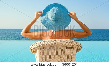 Woman Relax Near Infinity Pool In Sunny Day