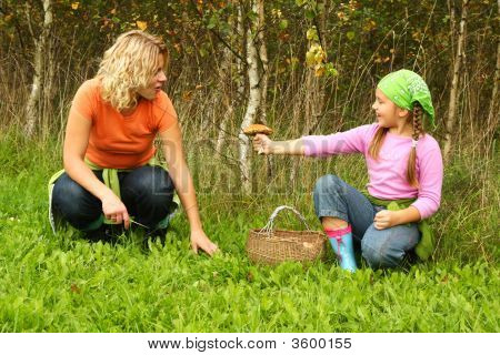 Mother And Daughter Picking Mushrooms