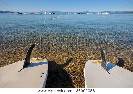 Two Paddle Boards On Shore Of Lake